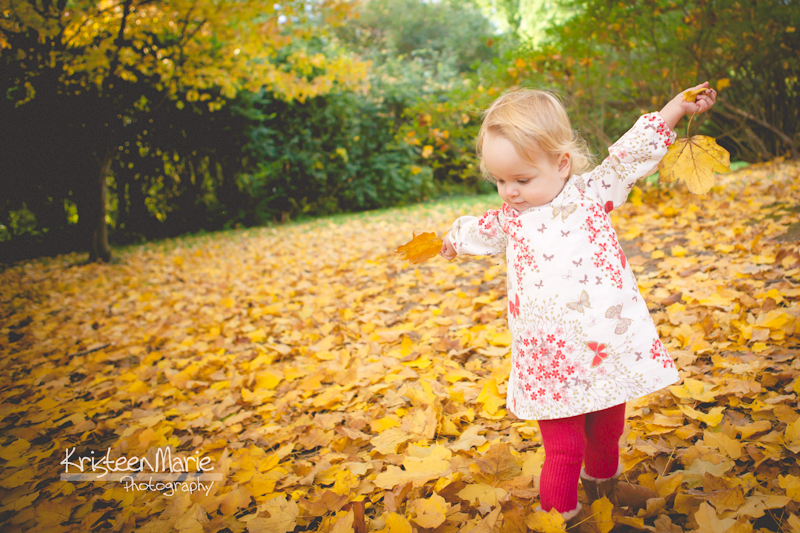 Kid playing in the Fall leaves
