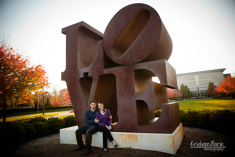 engaged couple in front of love statue in indianapolis