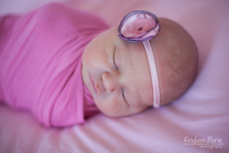 Newborn in pink wrap and hairband