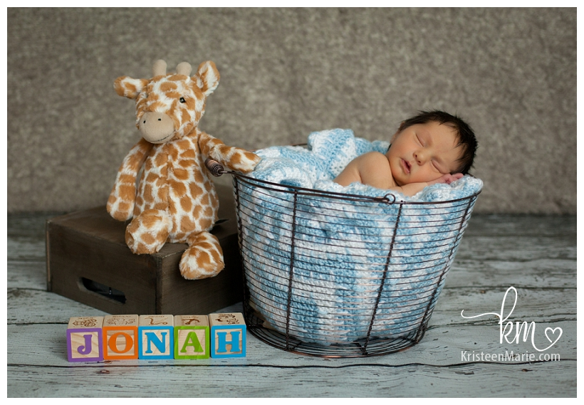 Baby in a bucket with letter blocks