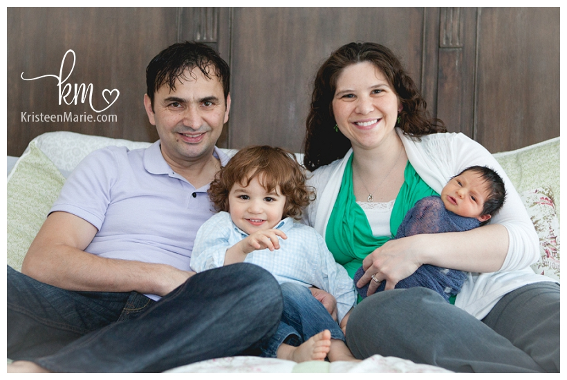 family with newborn baby on bed