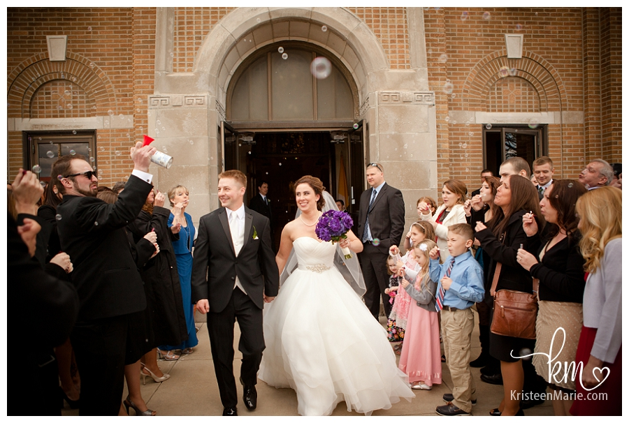 Bride and groom walking out of church with bubbles
