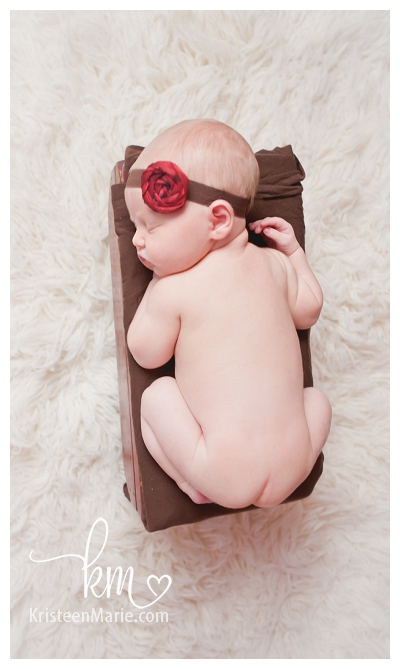 newborn girl in red and brown