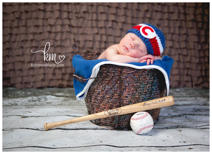 newborn picture with bad and basebal in basket
