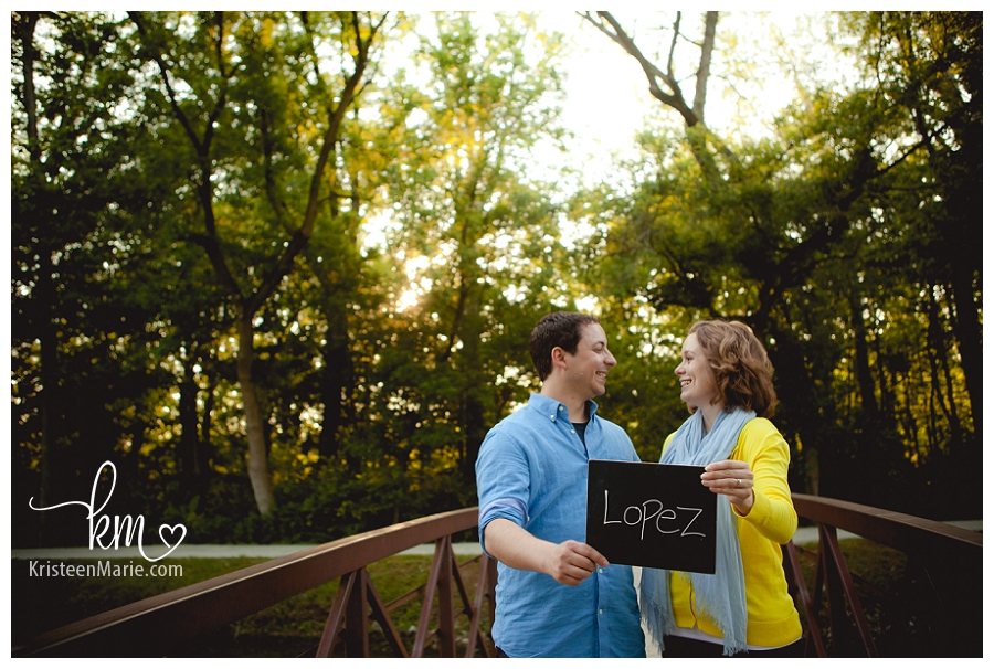 engaged couple on bridge with chalkboard