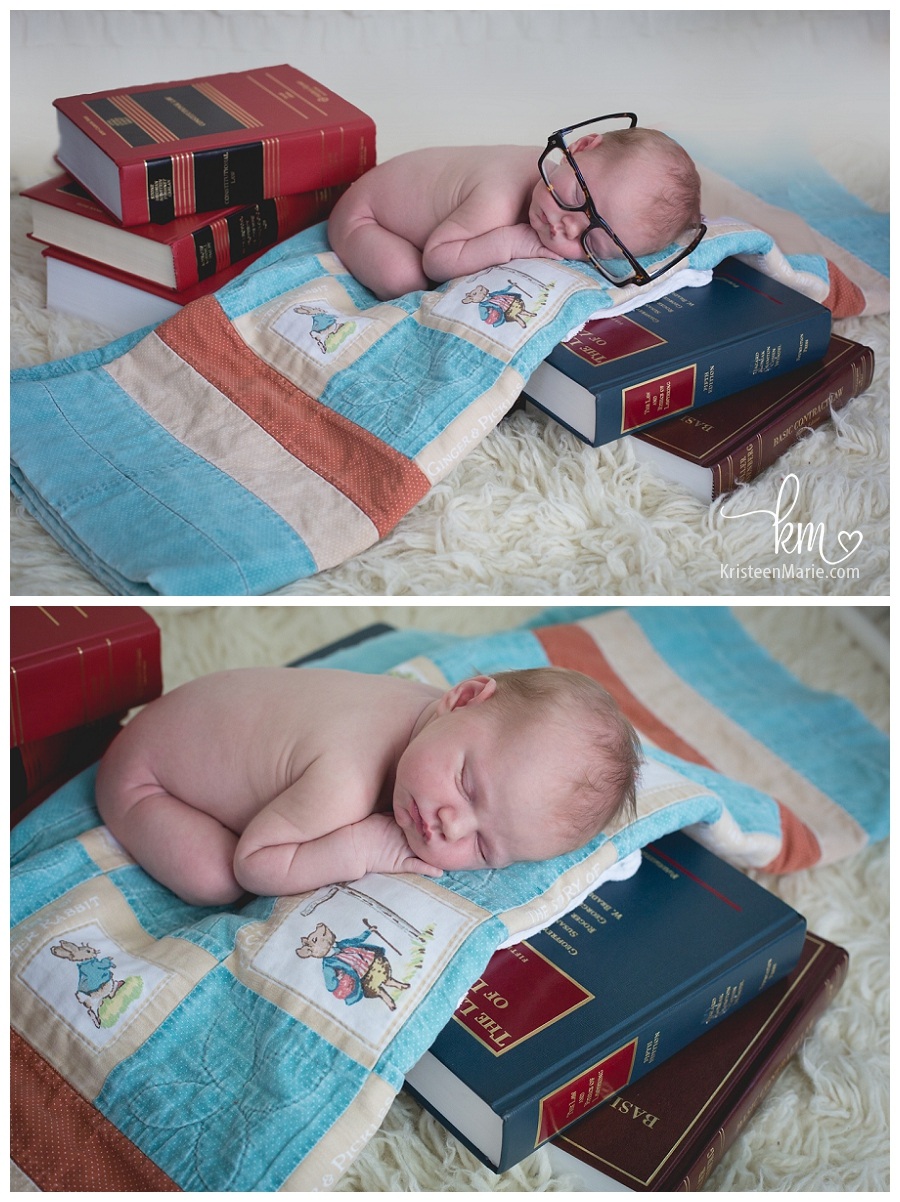 newborn on books with glasses