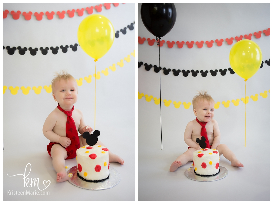 Little boy smashing Mickey Mouse cake
