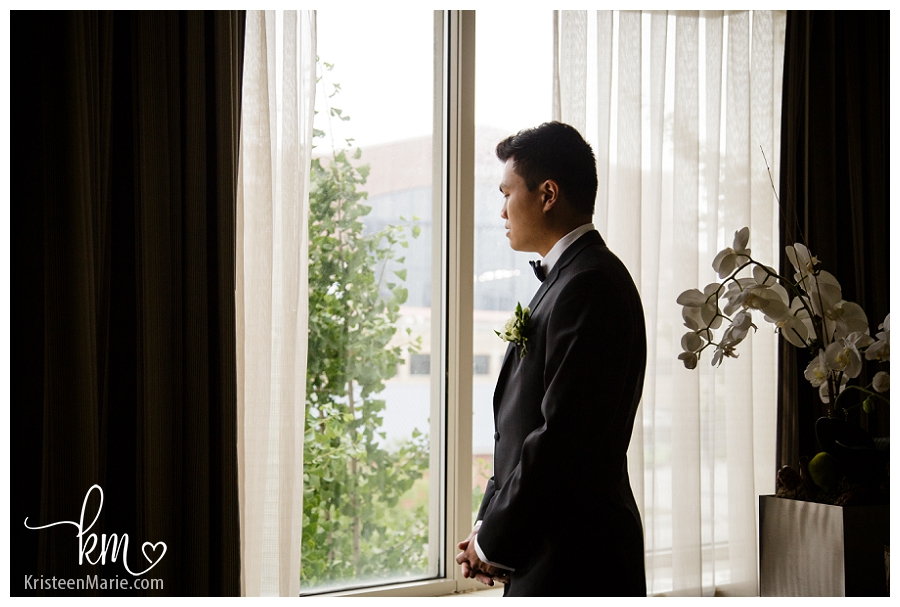 groom looking out window at Omni Hotel