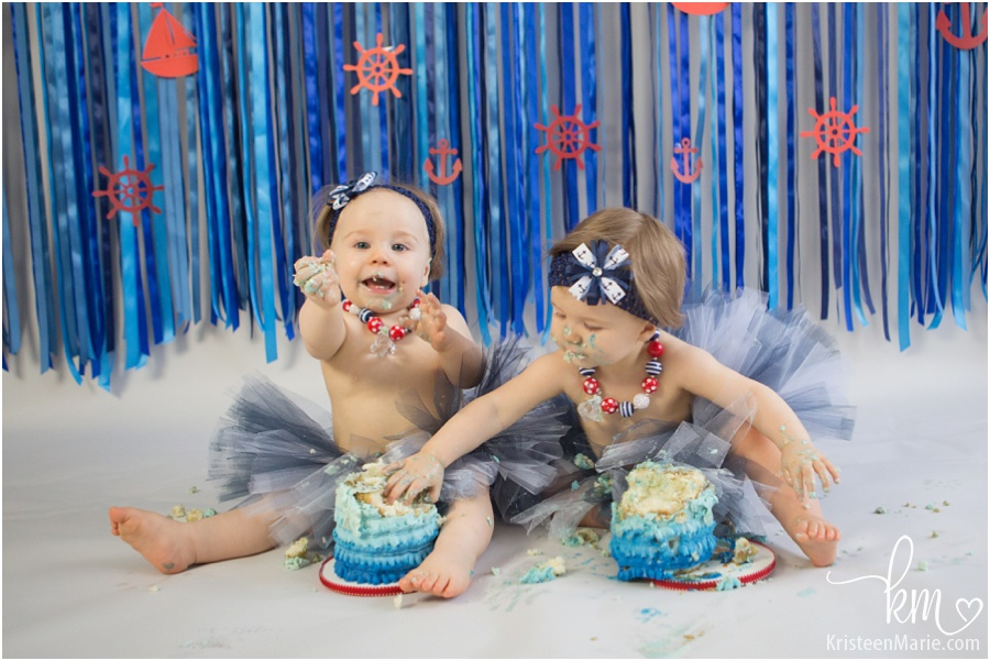 twin girls sharing birthday cake