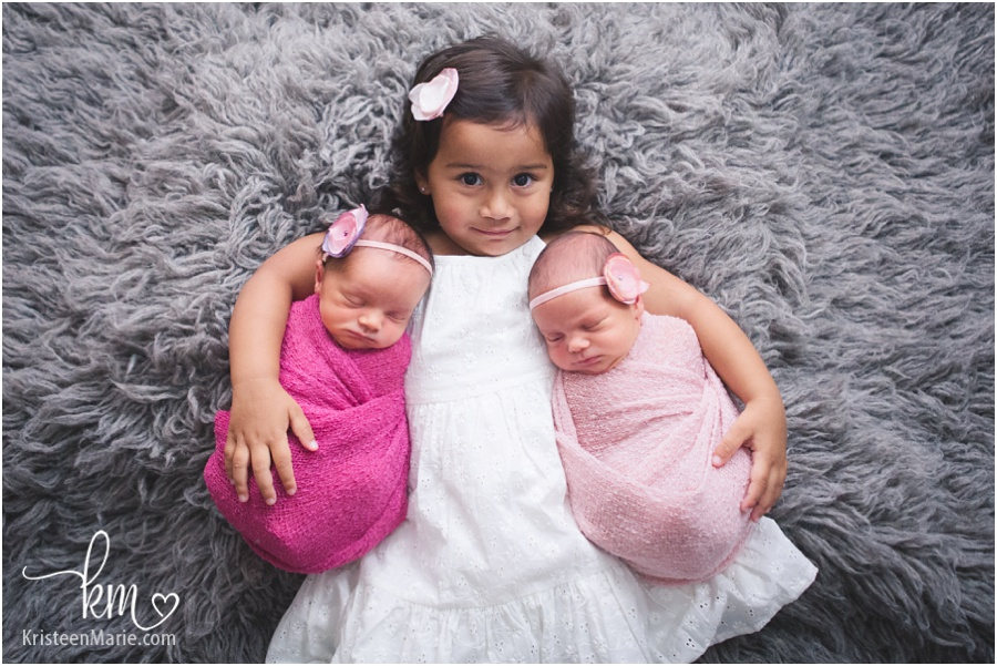 Big sister with twin newborn girls