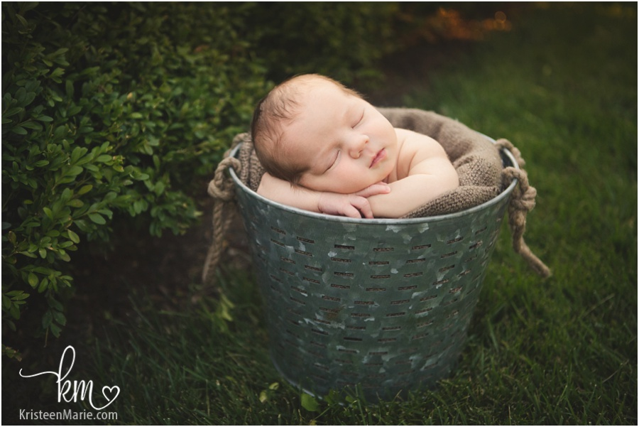 newborn photography outside - baby in a bucket in grass
