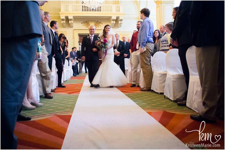 Bride waling down isle with dad