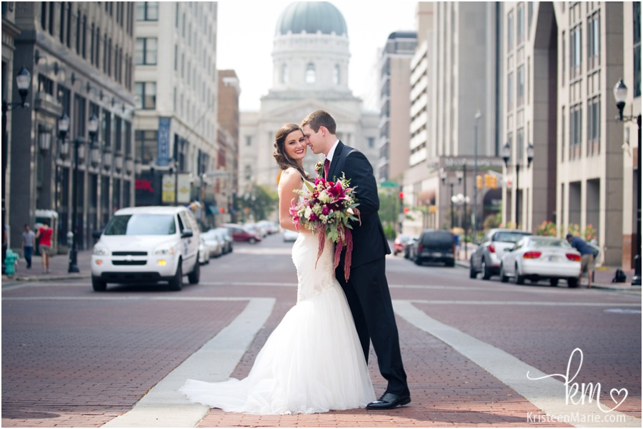 Bride and groom downtown Indianapolis wiht State House behind them