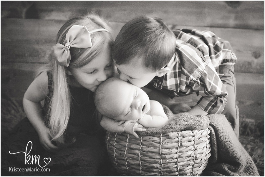 siblings kissing newborn brother in basket