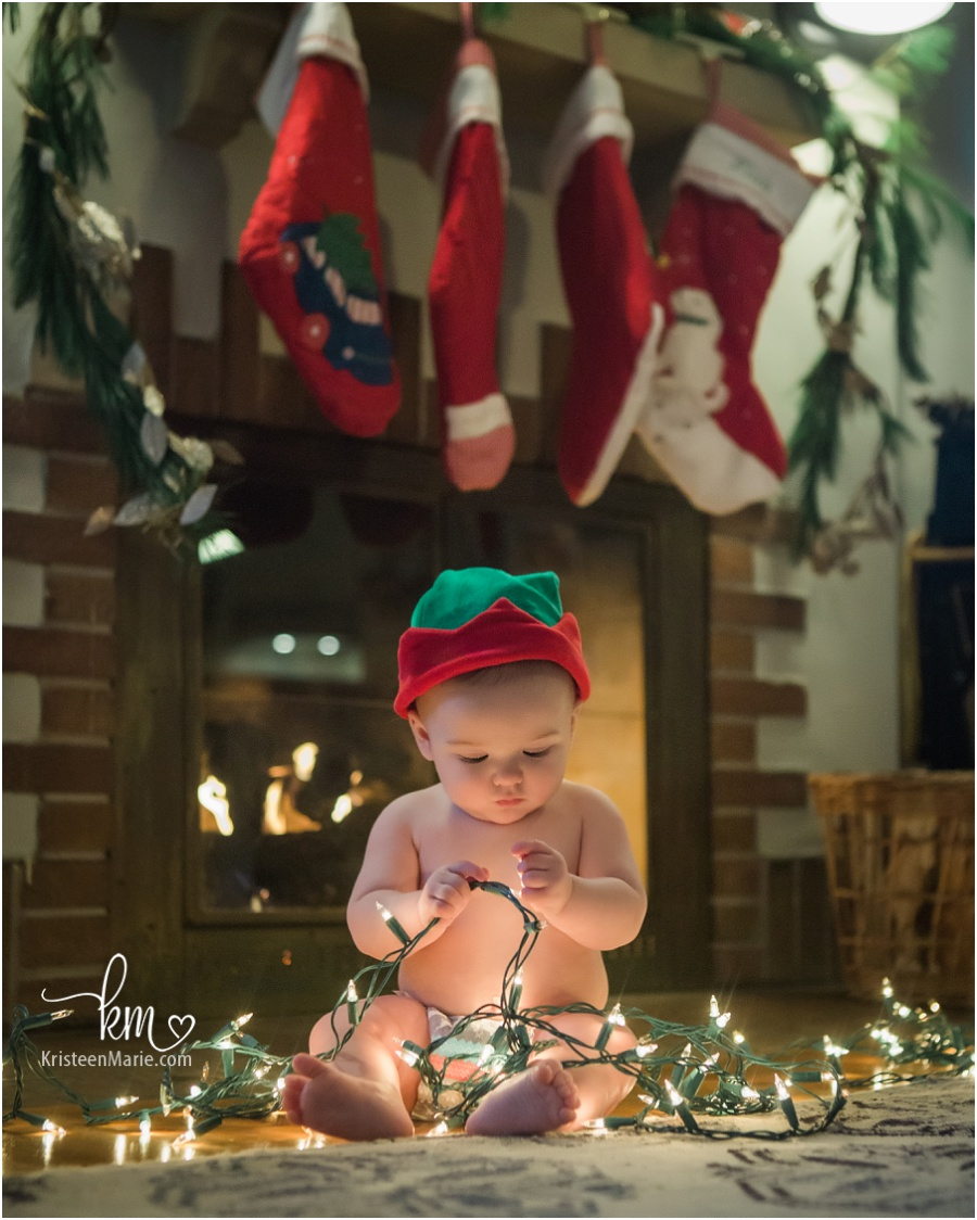 little boy with Christmas lights in front of fire place