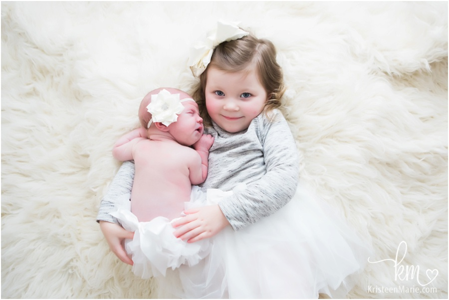 hugs from big sister to newborn baby girl