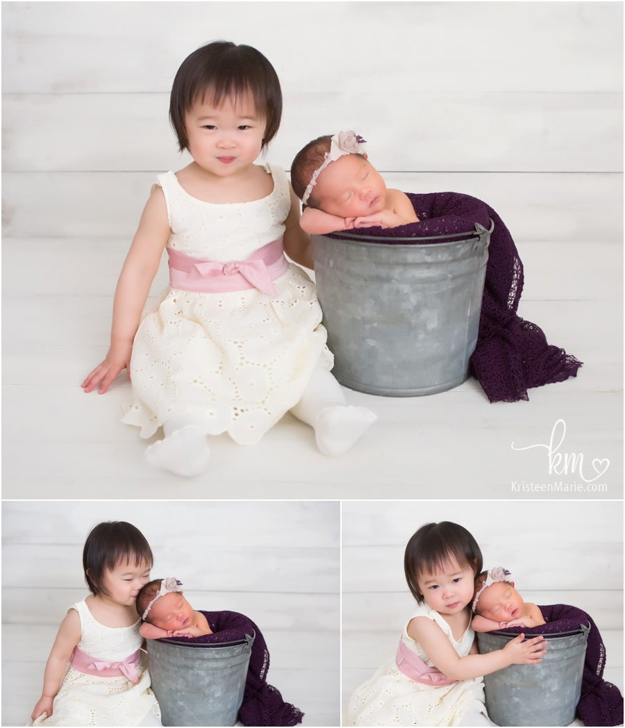 sibling with newborn baby sister in bucket
