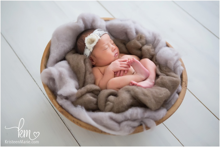 sleeping newborn baby in bowl with fluff