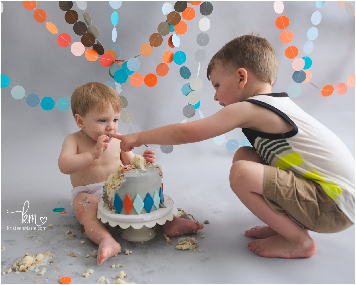 big brother showing little brother how to eat cake