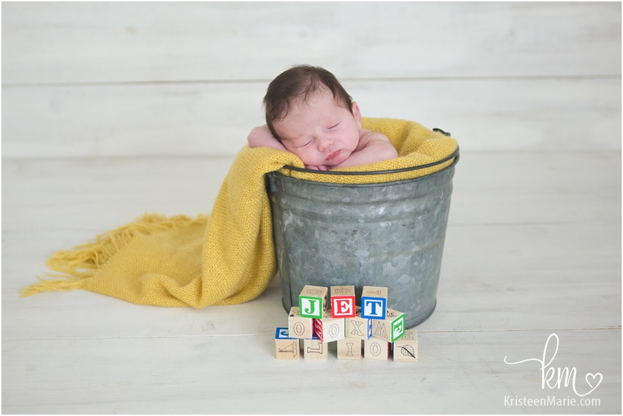 baby in a bucket with name blocks in front