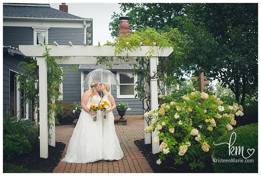 brides kissing at Mustard Seed Gardens
