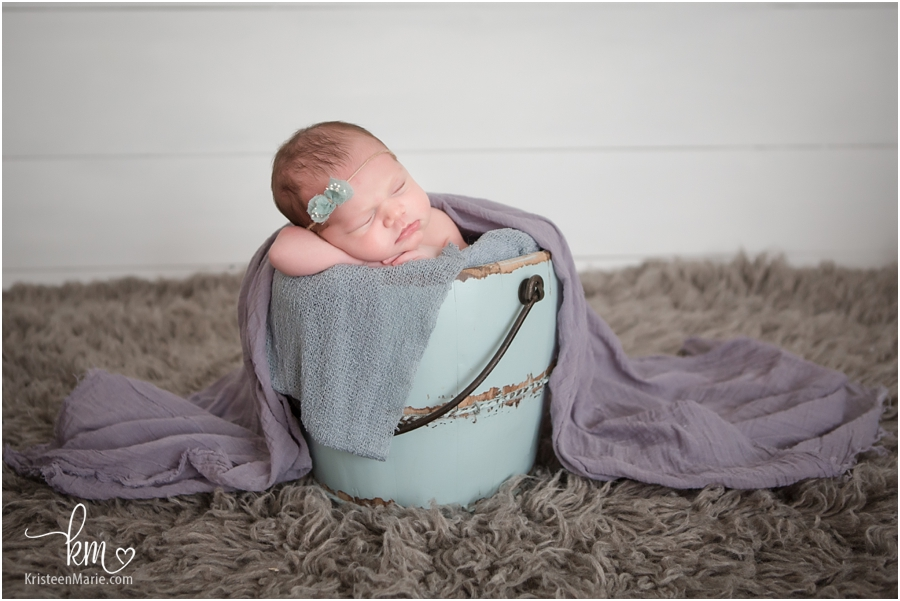 Pose zionsville newborn photography baby in a bucket purple and teal
