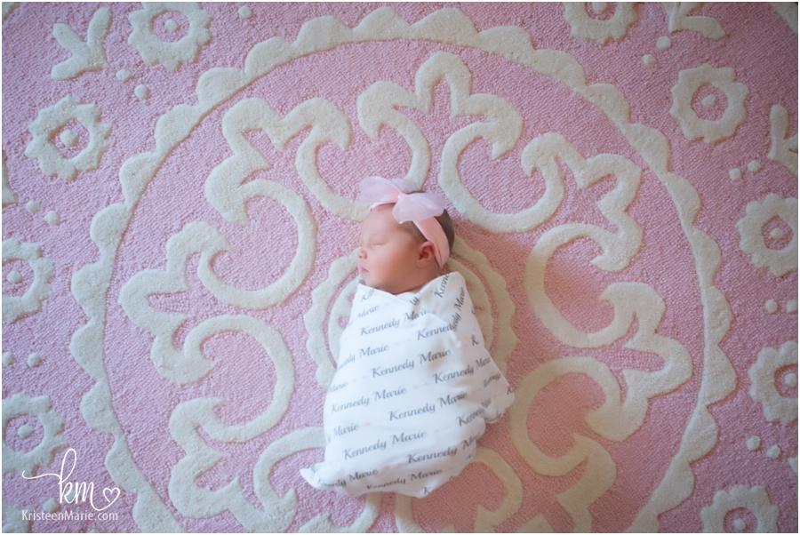 sleeping newborn girl on pink rug