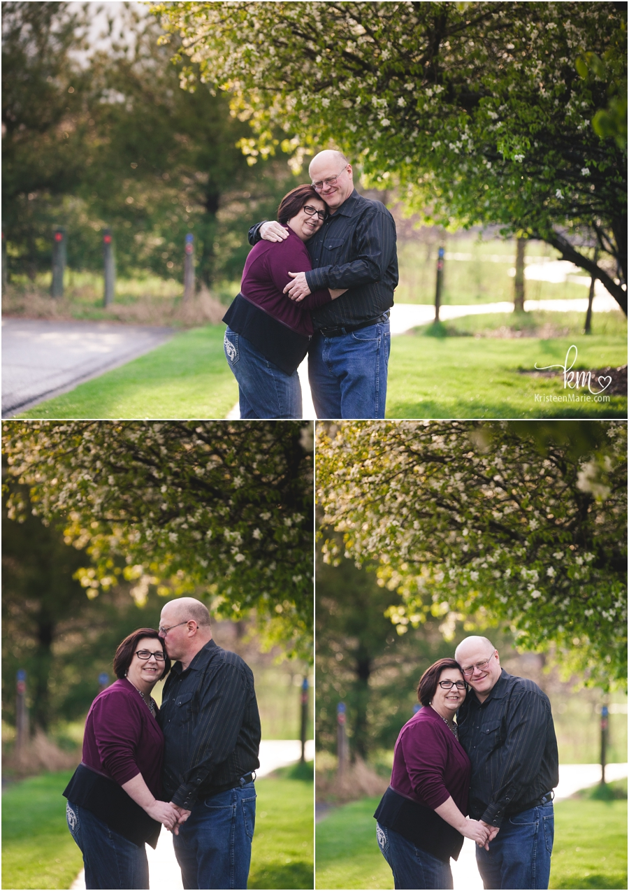 couple hugging under a tree in Indianapolis for engagement pictures