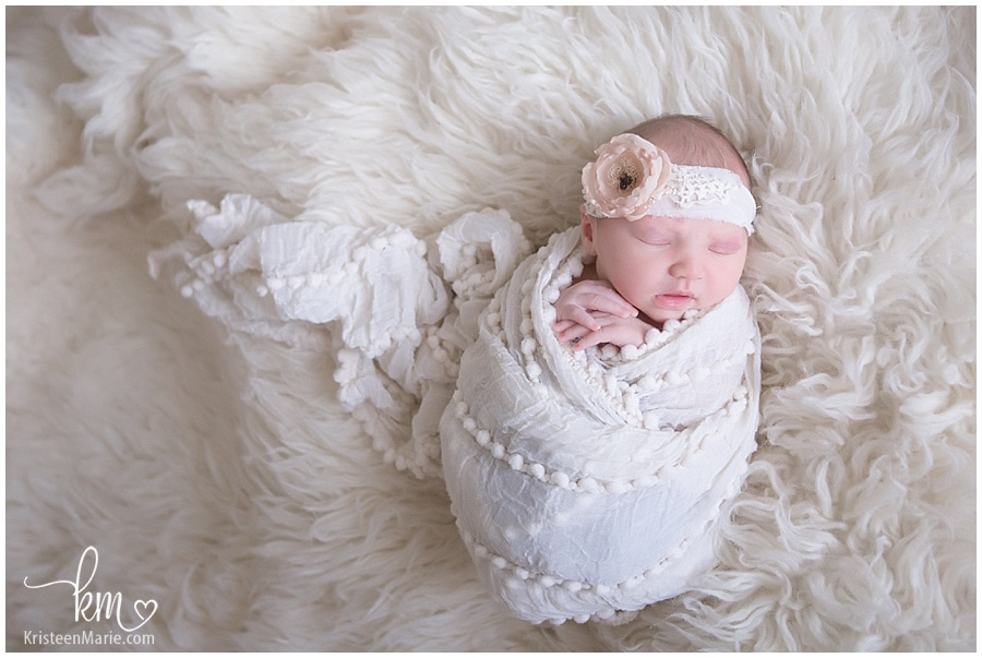 Indianapolis newborn photography newborn baby wrapped in white with flower headband