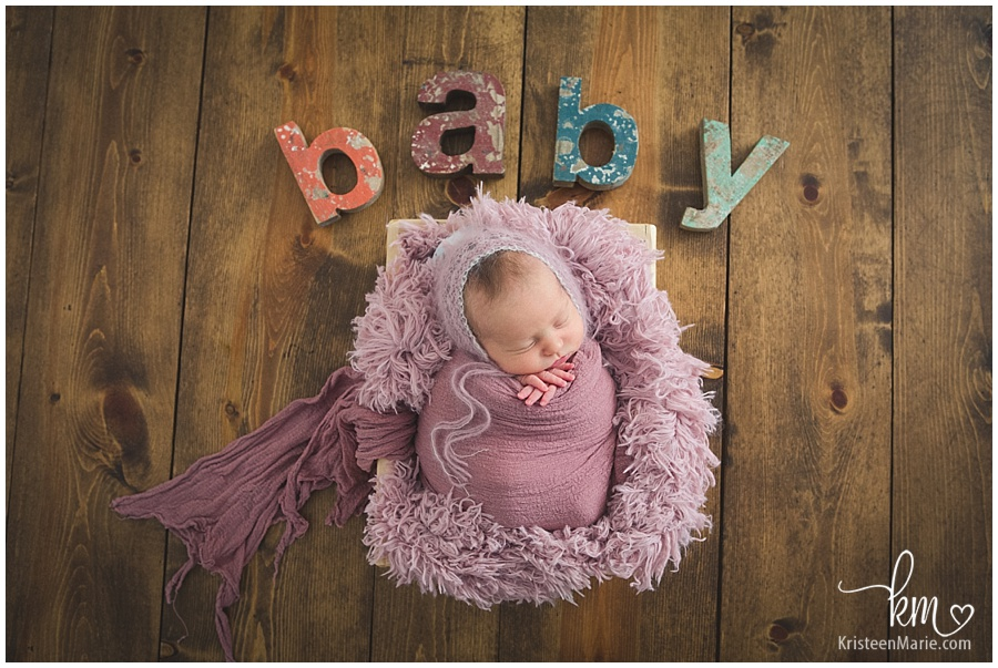 snuggly baby in pink blanket in a box with wooden floor