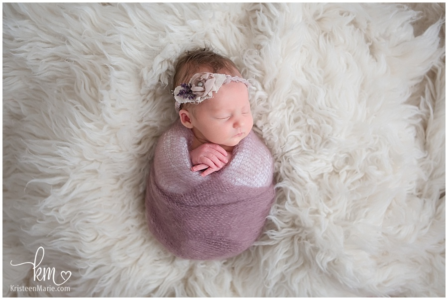 newborn baby girl wrapped in pink on white blanket/ little newborn peanut baby