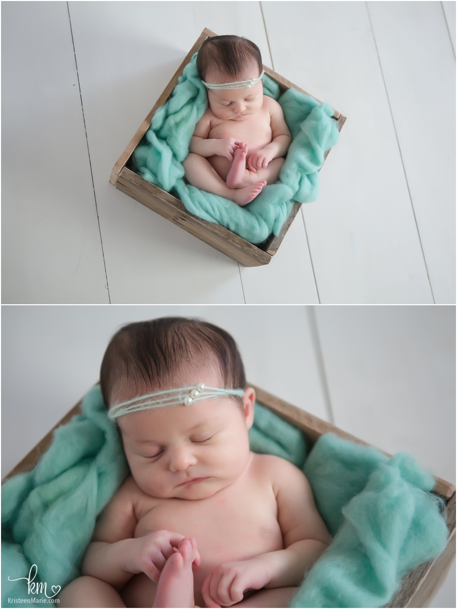 newborn baby in a box with teal blanket