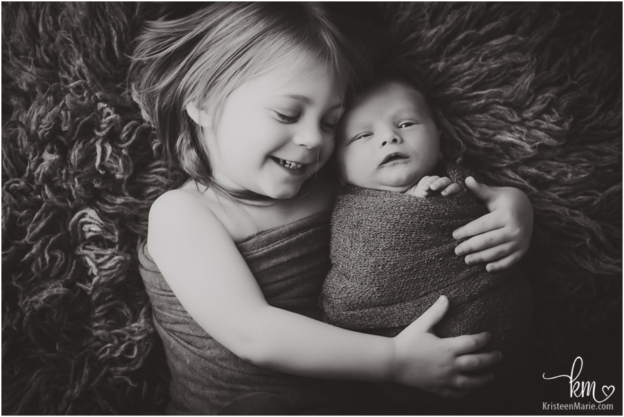 cuddles with new baby - sibling picture in black and white