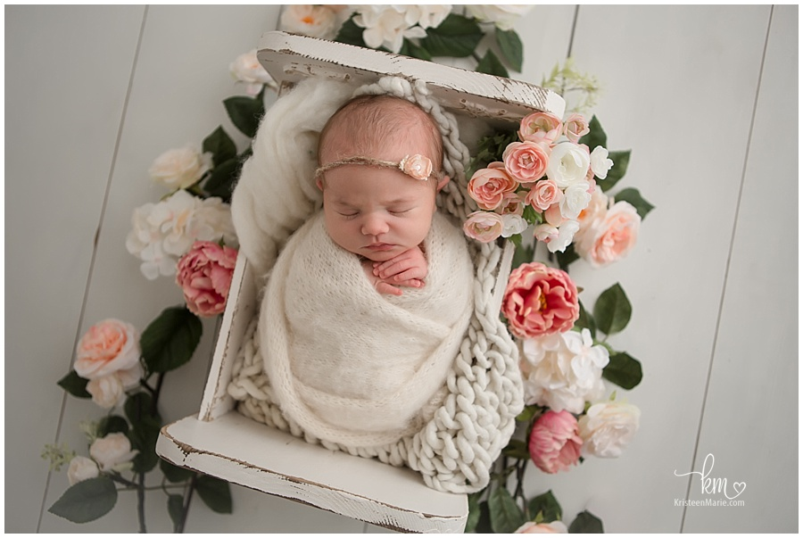 newborn in white crib with flowers