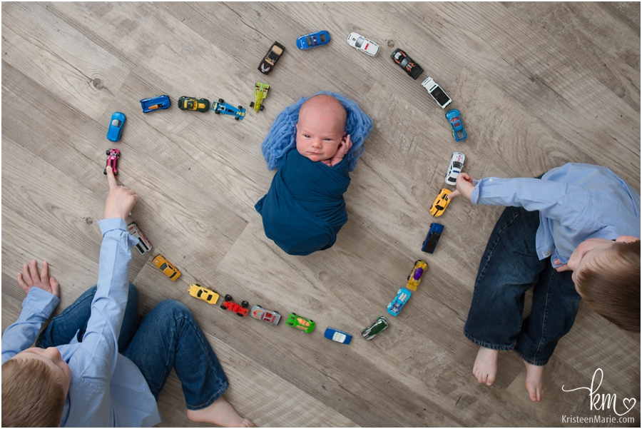 newborn baby surrounded by cars in heart - adorable sibilng shot with newborn and older siblings