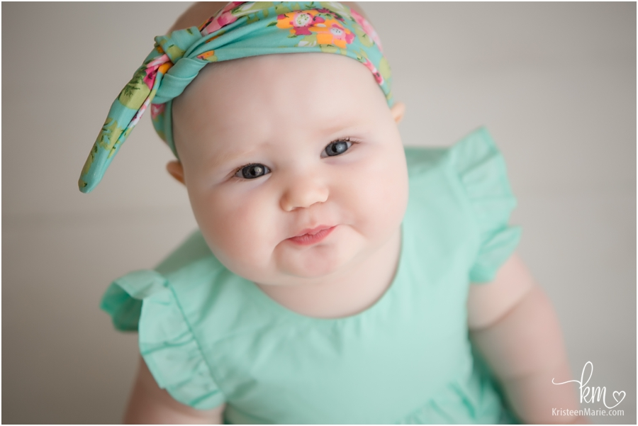 baby with teal and flower headband