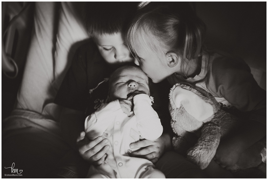 kisses to new baby from big brother and sister in hospital