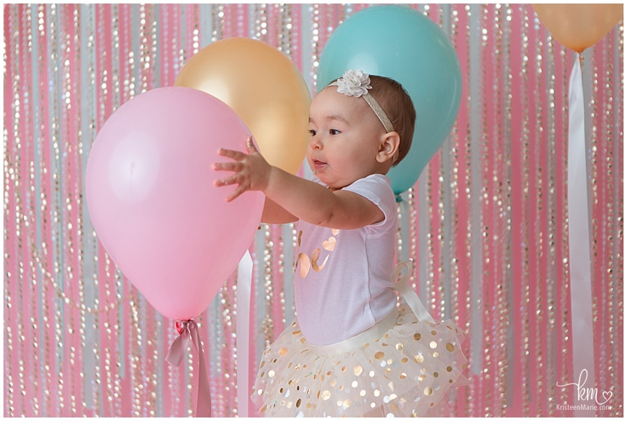 first birthday playing photo with balloons