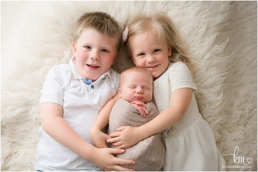siblings laying down with newborn baby - 3 kids