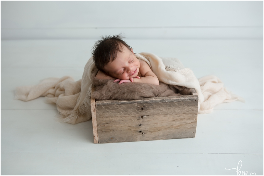 smiling newborn baby boy in a box