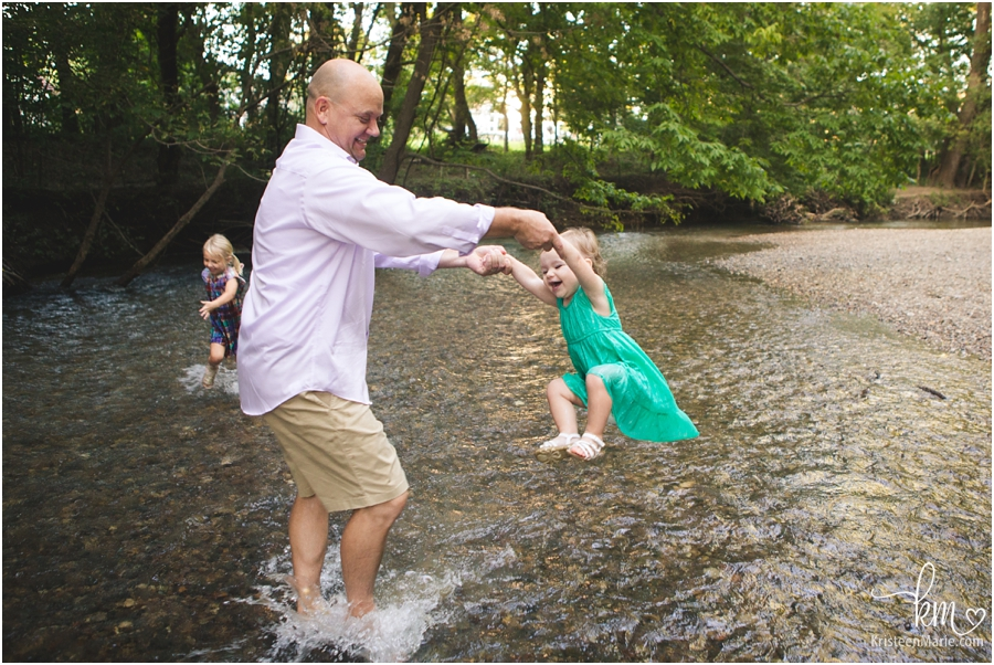 dad playing with kids in the creek