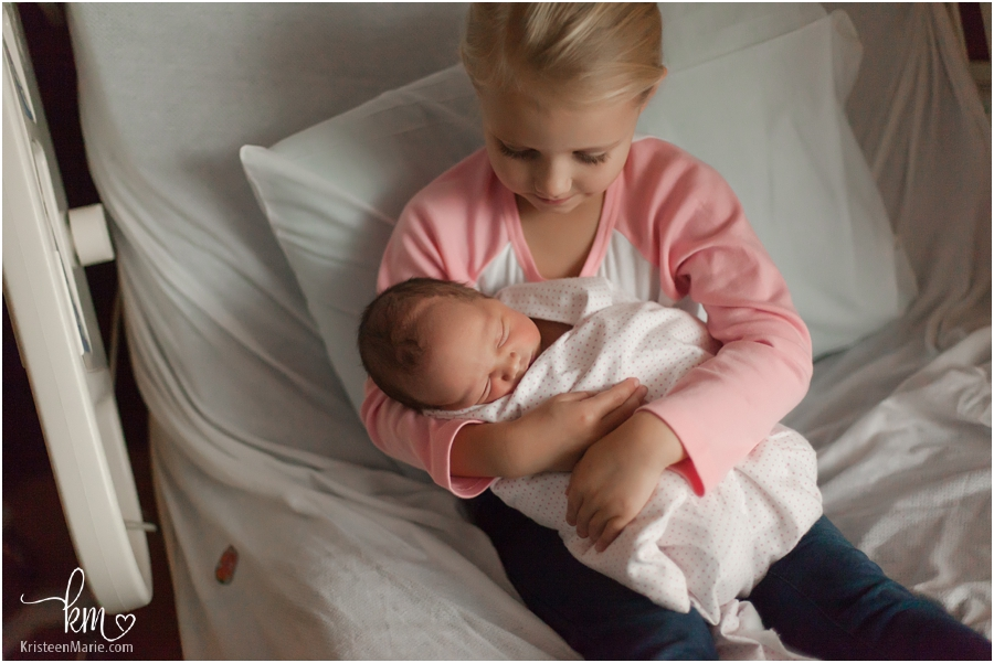 big sister holding newborn baby sister