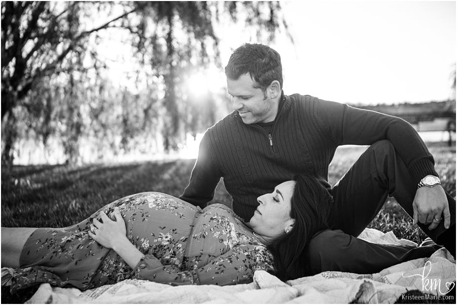 couple laying down for maternity picture - black and white image
