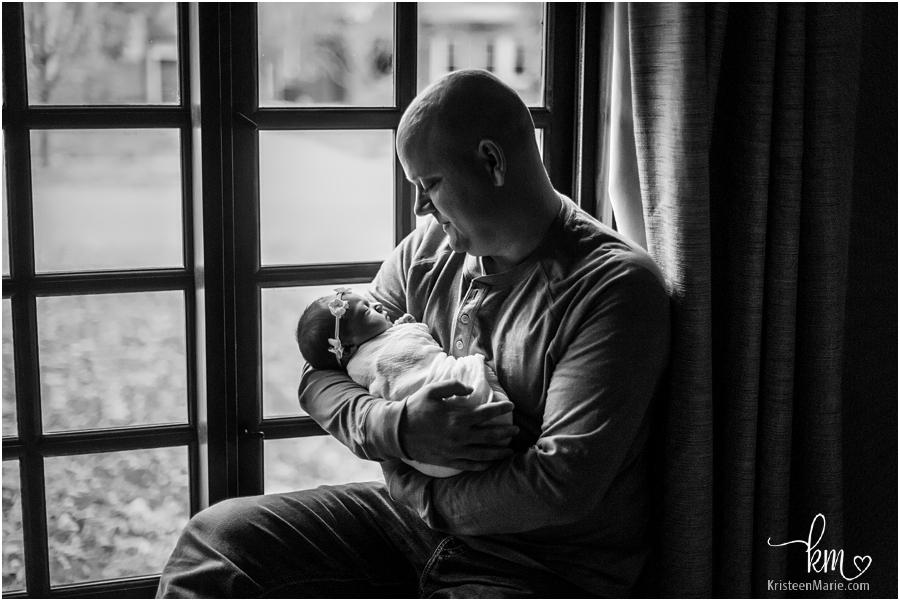 dad cudding newborn in front of window - black and white image