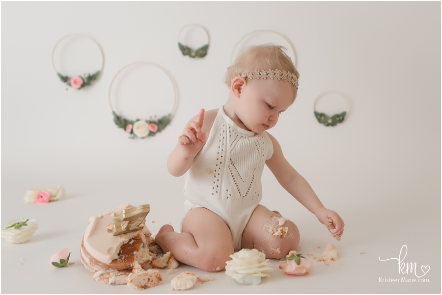 one-year-old posing for the camera - boho cake smash session