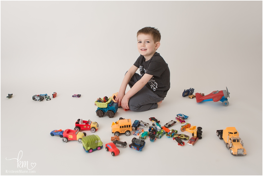 boy playing with cars in photography studio on white backdrop