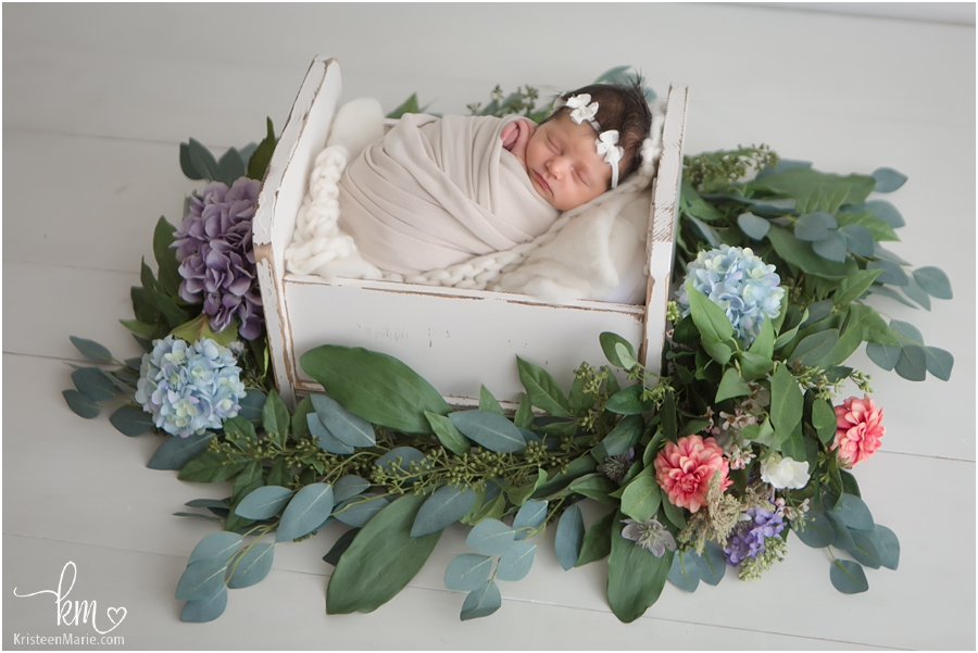 newborn baby with greenery and flowers