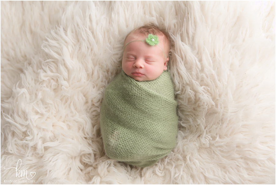 Sleepy newborn baby girl in green