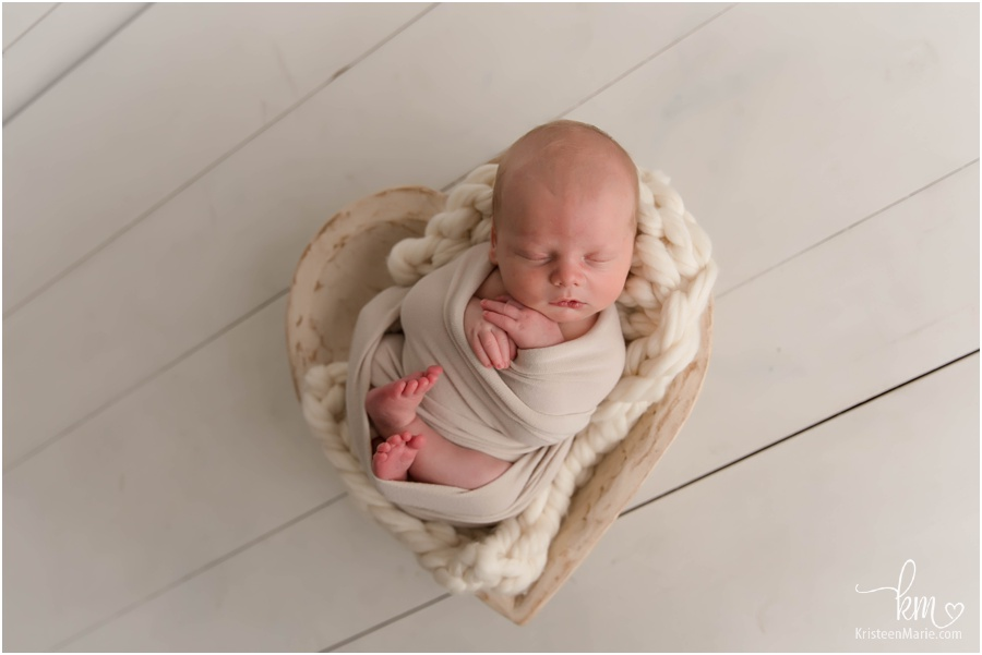 newborn baby boy in heart bowl