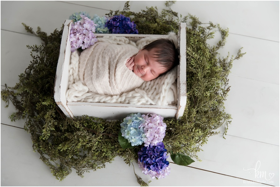 smiling newborn girl with flowers